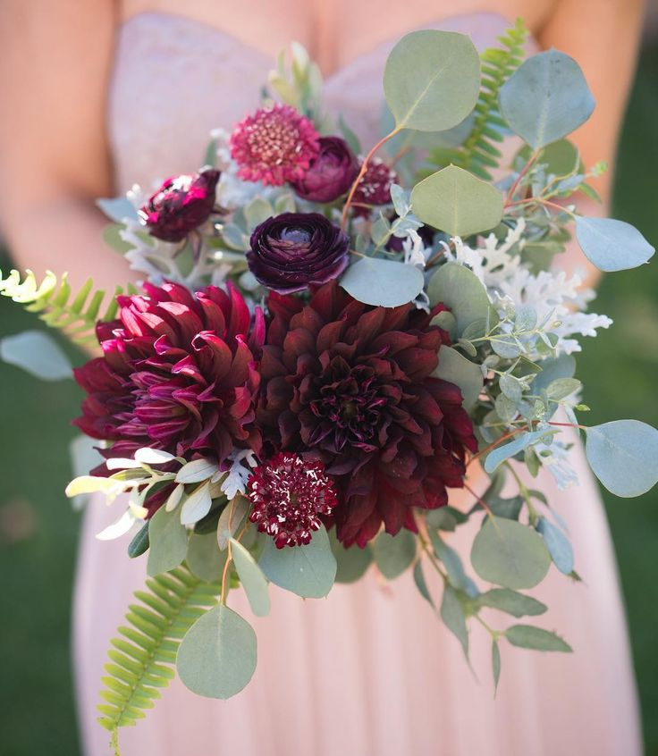 Marsala bridesmaid bouquet featuring burgundy ranunculus, dahlias and scabiosa with lush eucalyptus, fern and dusty miller. Photo by Nate and Jenny Weddings