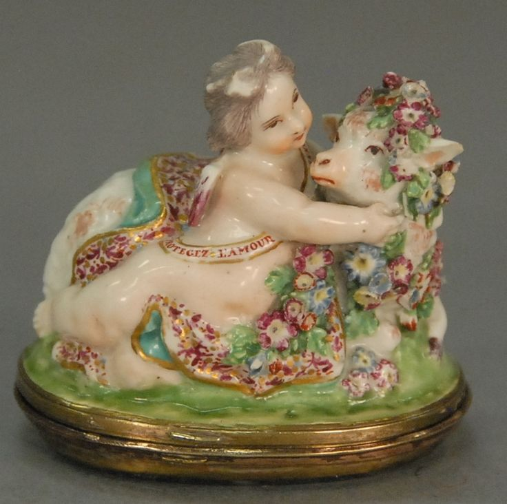Bonbonniere Chelsea porcelain figural putti with ribbon, inscribed in French Protecez L'Amour with recumbent sheep having spinach green agate hinged base (from 1760).  lg. 2 1/2 in. - Realized Price: $3,600.00