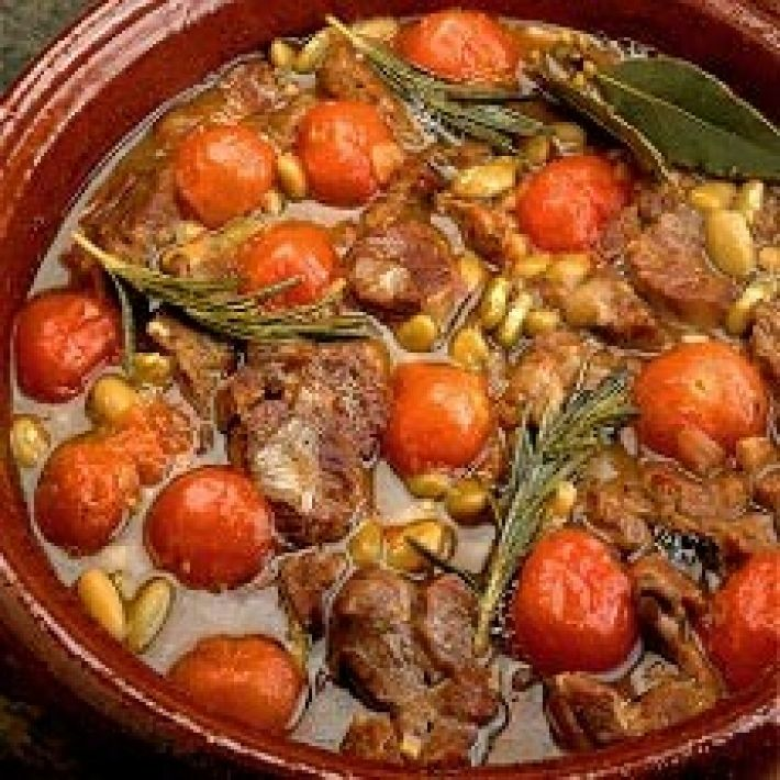 BRAISED LAMB WITH FLAGEOLET BEANS    lamb neck fillets, 8 oz (225 g) cherry tomatoes, 8 oz (225 g) flageolet beans, 2 large onions, 2 cloves garlic, 1 oz (25g) plain flour, 1 level dessertspoon chopped fresh thyme leaves, 3 small bay leaves