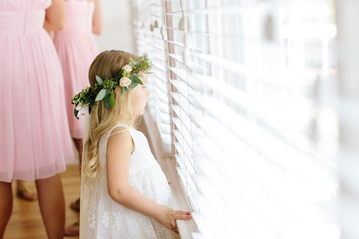 a sweet flower girl is ready in her flower crown of seeded eucalyptus, peach roses and ligustrum blooms, with streamers of cream satin ribbon.