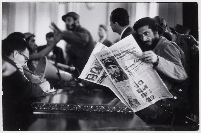 A Cuban revolutionary reads a newspaper as Fidel Castro gives a press conference in the background 1959 Cuba [700 x 463]