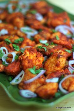 Tandoori Fish Kebabs  1 lb salmon belly, cut into bite size pieces (I have found salmon belly to work best for this recipe)  1/2 cup all purpose flour, with a pinch of salt and 1/2 teaspoon chili powder mixed in  2 teaspoons tandoori masala (I prefer Rajah brand)  1/2 teaspoon of ground black pepper  Salt to taste  2 teaspoons garlic paste  2 teaspoons ginger paste  Juice of 1 lime  cooking oil  Sliced onion and chopped cilantro for garnishing 4-5 lettuce leaves for serving (optional)