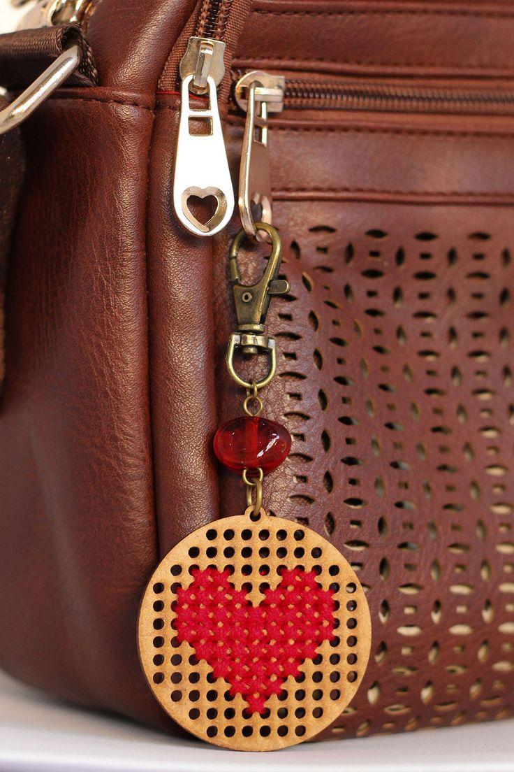 Chaveiro bordado à mão com ponto cruz, pingente redondo e bordado de coração.  Com detalhe da conta de vidro vermelha e fecho de mosquetão ouro velho.