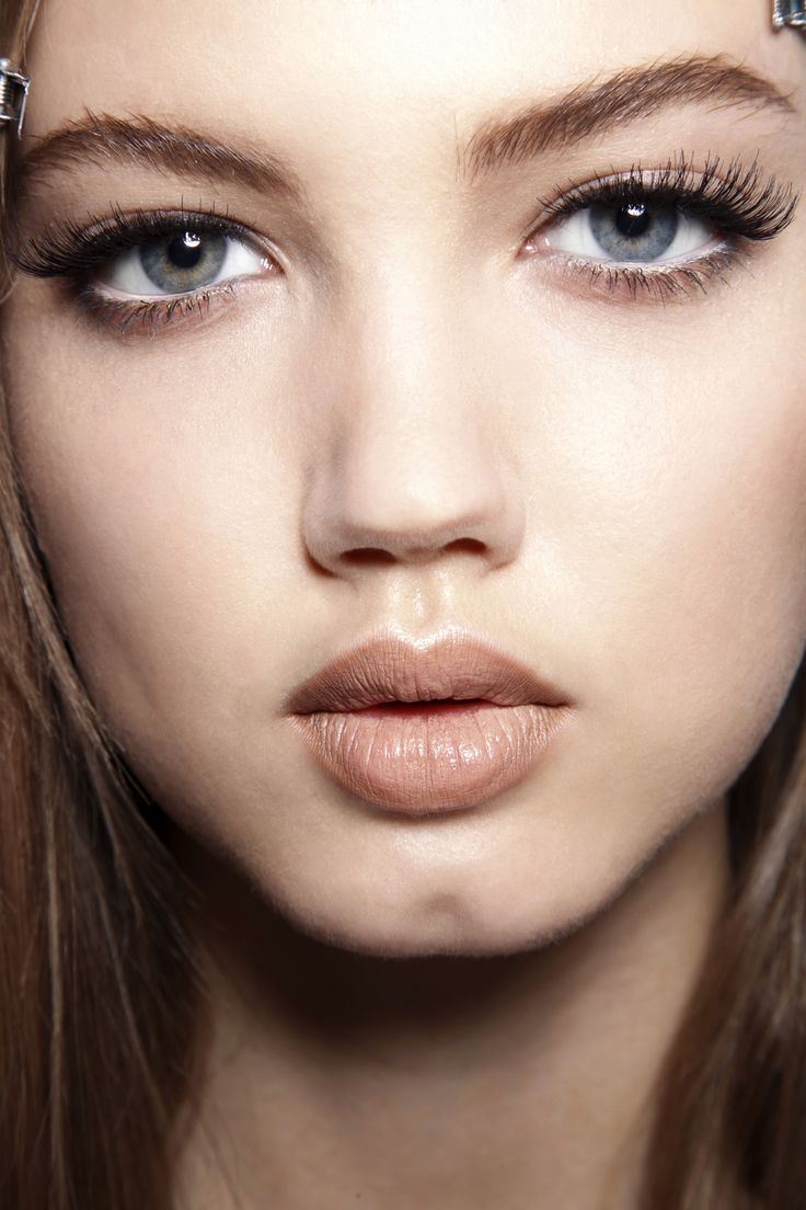 Soft shimmer on the eyelids, peachy tones, and opaque nude lips.