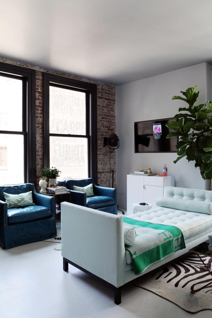 Multiple patterns, materials and colors coexist in this sophisticated, chic loft space. Blue leather club chairs and a tufted white bench provide ample seating.