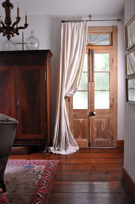 """Beautiful French Cypress Doors with early 1800's door hardware are adorned with  a woven old linen sheath from France.  early Louisiana 1820s beehive armoire. The floors are 2"""" x 12"""" ceiling joist from a school house demolition in the nearby town of Donaldsonville, Louisiana. A. Hays Town"""