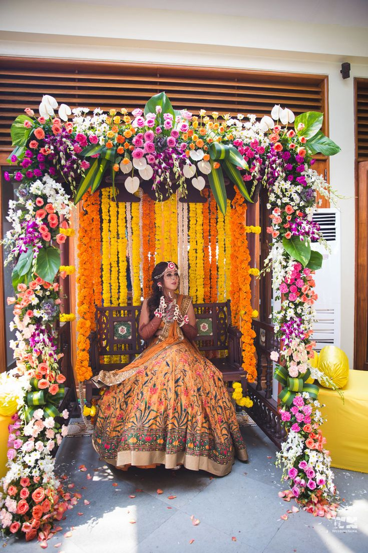 Colourful floral décor for a mehendi seat set up. | WedMeGood|#wedmegood #indianweddings #mehendi #mehendidecor #floraldecor #mehendiseat #mehendiswings #swingdecor