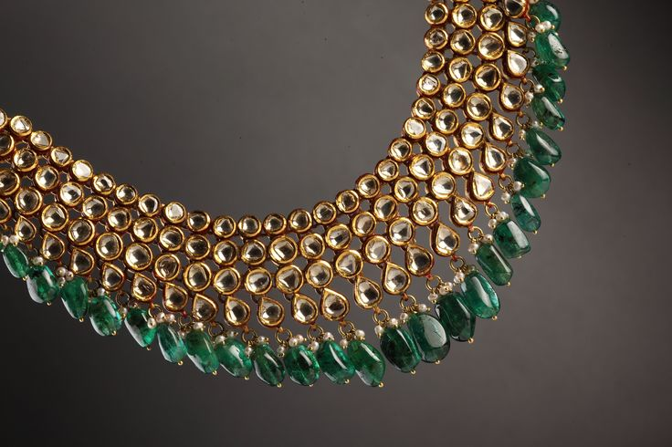 Look decadent and delightful in this beautiful kundan and emerald necklace.  White teardrop kundans are combined with round white kundans for a charismatic effect. Emerald brings an antique look to this classy necklace.