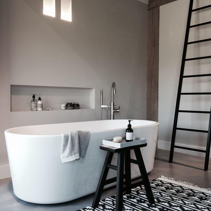 Nis in de muur voor stijlvolle opbergruimte, losstaand bad, landelijke stijl in de badkamer, trap ter decoratie.