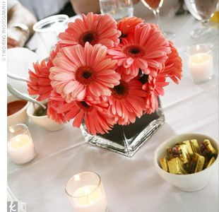 Gerbera daisies, with colored paper wrapped inside the vase. Would do ribbon outside of vase, with maybe mirror under it. Votives around