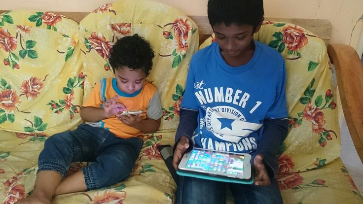 Two brothers busy playing with tablets...