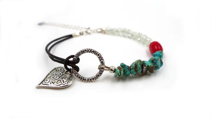 Bracelet constitué d'un cordon de cuir brun, de chips de Turquoise reconstituée, d'une olive rouge en Bambou, et de perles de verre craquelé. Il est orné d'un anneau et d'un…