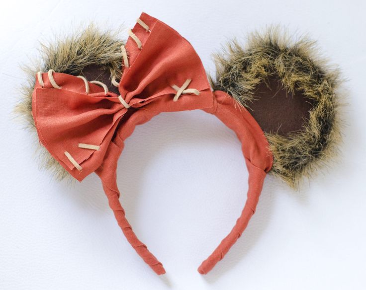 Mickey Mouse Ear Headband Inspired by Star Wars Wicket Ewok  These ears are covered with a brown faux fur, brown felt, and red-orange fabric. The ears are accessorized with a bow made of red-orange fabric and light brown leather string. (Fits adults & some children)  These are perfect for any Disney vacation, and are sure to make you stand out at the Parks