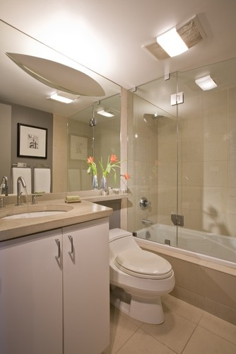 Modern White Bathroom Design Nin Small Space With Simply Sink Cabinet And Wide Mirror Also Toilet And Concrete Bathtub With Glass Panel Decorated By