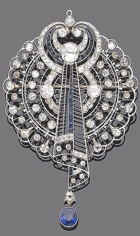 An early 20th century sapphire and diamond brooch pendant The openwork plaque of fine knife-wire, millegrain set brilliant and single-cut diamond detail, its centre issuing a stylised scroll of similarly set diamonds and calibré-cut sapphires, to an oval mixed-cut sapphire drop, diamonds approx. 4.00ct. total, length 8.0cm.