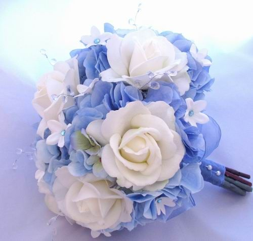 This bouquet features natural touch white roses accented by silk blue hydrangea, blue rhinestone centered silk stephanotis, and clear faceted sprays accented by a sheer blue billowing bow partial stem wrap with a white pearl seam.