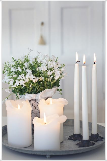Candle light tray with different sized candles and white flowers. Love the star base candle holders!