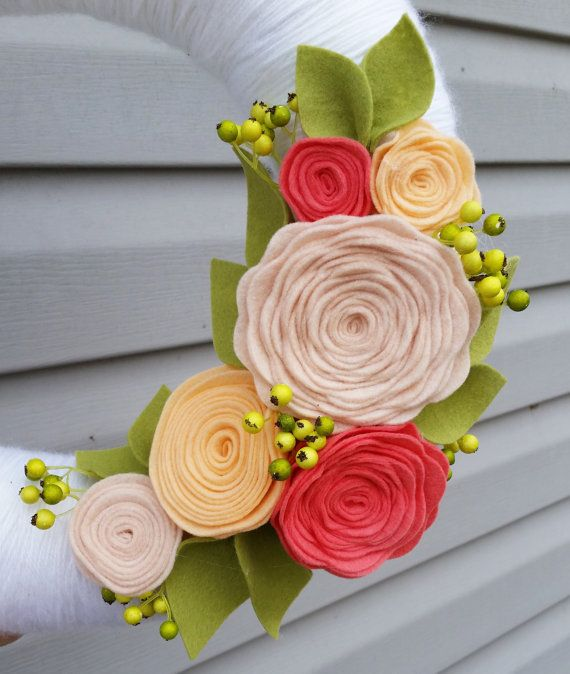 This wreath (shown in 12) is wrapped with a clean white yarn and embellished with a beautiful array of coral, peach and blush flowers. Beautiful bright