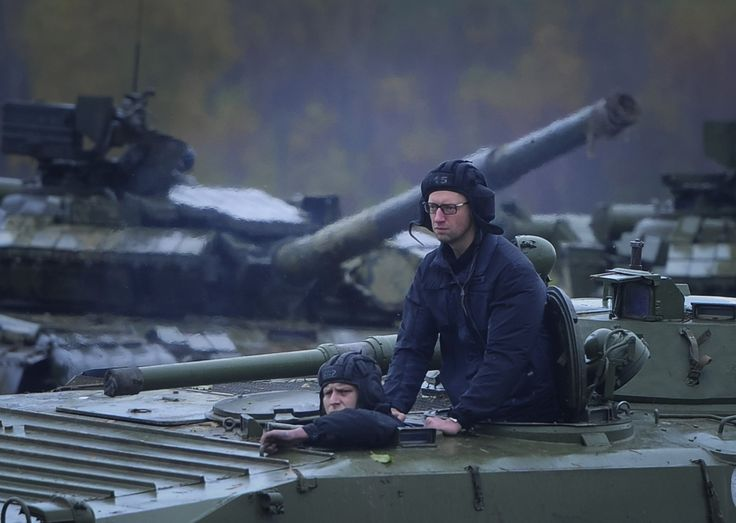 Ukrainian Prime Minister Arseniy Yatseniuk (standing) rides on an armored personnel carrier during a visit to the International Center of Peacekeeping and Security in Yavoriv, west of Lviv. (Reuters/Andrew Kravchenko)