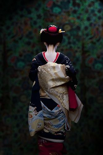 A young maiko. Look at the low red collar, the long sleeves, and the long elegant obi draping down the back.