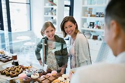 Mother and daughter talking to worker in bakery