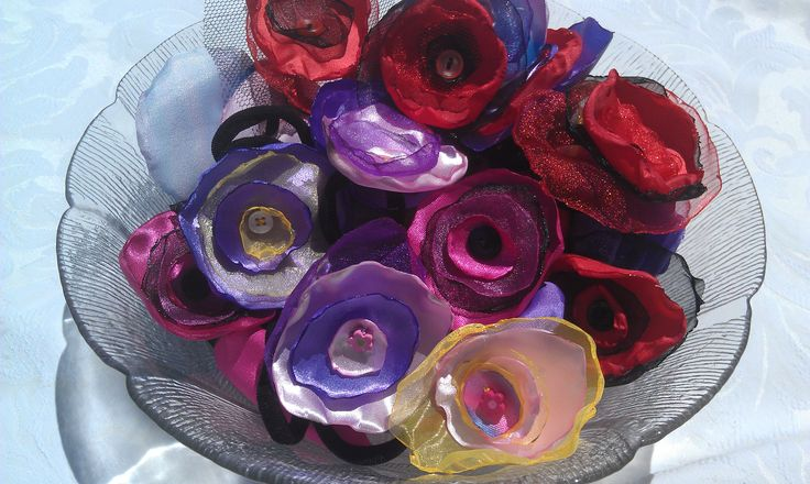 Hair elastics and clips.  Synthetic fabric curled using flame, button stitched. Donated by Julia Playford  Cheers. $2.50