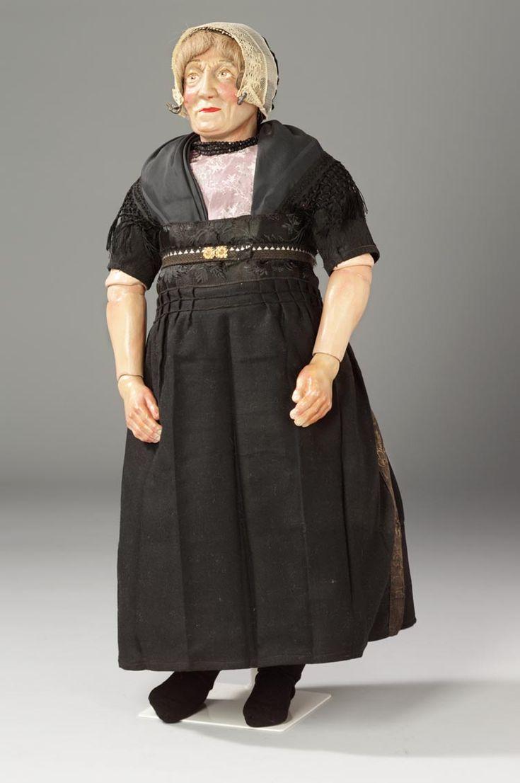 Klederdrachtpop uit Urk, 1930 Zondagse kleding. Ondermuts, oorijzer en hul met gegeelde kant en dessien - haar met rol aan voorzijde. Glasgranaten ketting. Onderborstrok, middelde, rose kraplap met ingeweven patronen, zwarte zijden doek met franje. Rood/wit/blauw gestreepte onderrok van baadjesgoed, een rode tussenrok en een grotendeels laken bovenrok. Het zondagse schort met gebloemd lint langs bovenzijde en zijkanten. Zwart schortband met witte spiegeltjes, goudkleurig gespje middenvoor…