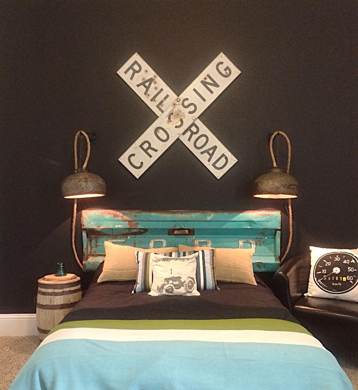 This little boy's room by Grace Grey Designs www.facebook.com/gracegreydesigns features a Ford tailgate headboard, railroad crossing sign, DIY industrial domes turned bedside hanging lamps, bedding from Ikea, and a chalkboard painted wall for creative little hands!
