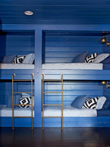 Adding built-in bunks (clad in V-groove pine to match the existing walls) turned unused space into a welcoming room. Navy paint adds to the cozy vibe.