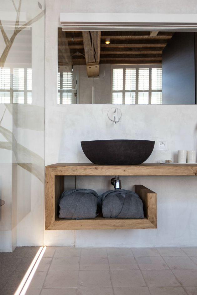 Un baño con mucho encanto para una casa rural: encimera de madera, lavabo negro y luz en mampara.