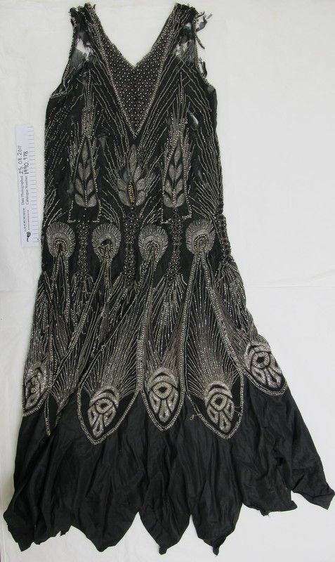 1920's beaded 'flapper' evening dress FromThe Kauri Museum  Matakohe Fine black crepe georgette sheath dress with heavy beading. Beading covers every inch of the crepe in clear glass, silver, black and gold, with floral and tear designs, with large peacock feather designs towards the skirt hem, where the material changes to taffeta with a handkerchief hem. Maker:Unknown Date Made: c.1920's