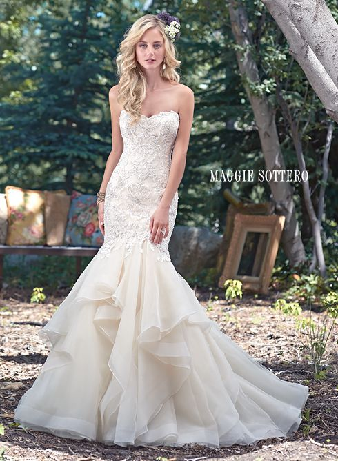 Malina wedding dress by Maggie Sottero | Understated drama is found in this fit and flare wedding dress with a stunning fitted lace bodice, accented with Swarovski crystals, and voluminous tiers of tulle and Chic organza layered throughout the skirt. Finished with sweetheart neckline and inner corset and covered buttons over zipper closure. Beaded lace keyhole coverlet sold separately.