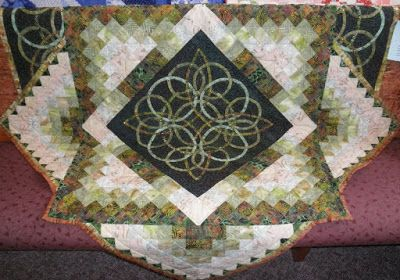 Celtic quilt at the Morris Quilt Guild show, 31 Mar 2017. Looks like it would hang in a shield shape. hand appliqued, with crystals on the rings