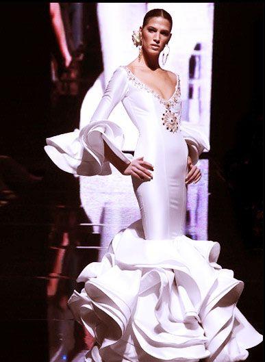 vestidos-de-novia-gitana-flamenca .Si lo que quieres es respetar al máximo el traje de flamenca, ya que te gusta su diseño, para un traje de novia, puedes probar con este vestido, ya que respeta al máximo un traje de flamenca pero se mantiene en blanco, para que lo puedas lucir en el día de tu boda. El escote es amplio y muy cómodo y sus volantes son enormes, para dar voluptuosidad al vestido.