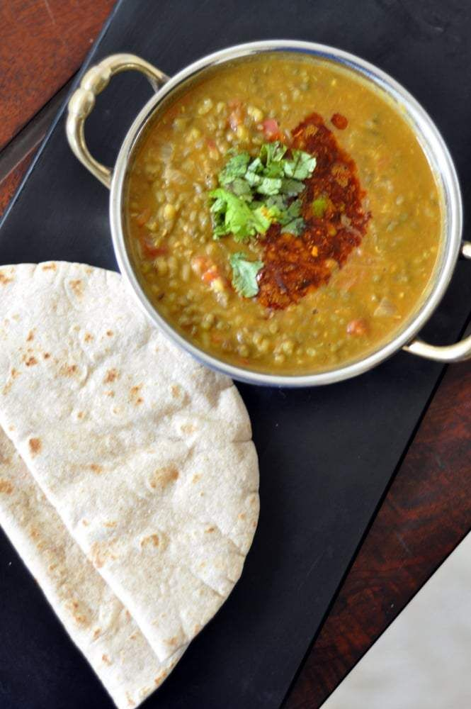 If there is one thing I love the most about Punjabi cuisine is its extensive use of dals aka lentils. There is no meal which passes by without a dal in the menu and there are no two days the same dal is made. This punjabi moong dal with onion, ginger, garlic and tomatoes is perfect for a winter meal