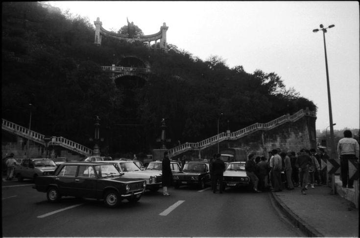 """Blokád az Erzsébet-híd budai hídfőjénél. A taxisok rendőri felvezetéssel átvonultak a Felvonulási térről a Kossuth térre. Éjfélig adtak haladékot a kormánynak, hogy visszavonja a döntést. Az esti bejelentést egyetlen kormánytag nem vállalta magára, helyettük egy szóvivő: Kardos Antalné közölte a 65 százalékos áremelést. A Parlament lépcsőjén Siklós Csaba közlekedési, hírközlési és vízügyi miniszter tárgyalt a taxisokkal. """"A kormány kényszerhelyzetben van, nincs mód a visszavonásra"""" –…"""