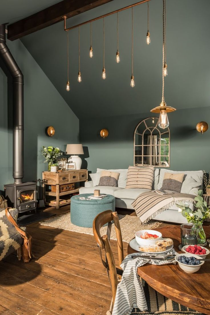 love the dark green colour of these walls paired with wooden dining furniture