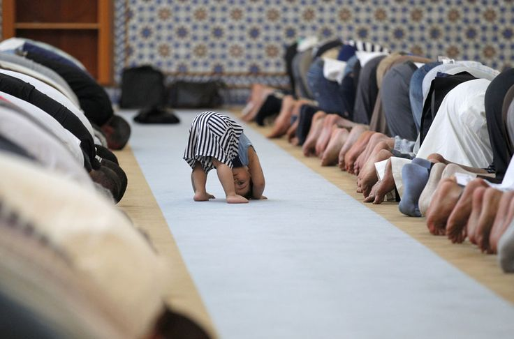 A child leans down near members of the Muslim community attending midday prayers at Strasbourg Grand Mosque in Strasbourg, France on the first day of Ramadan, July 9, 2013.