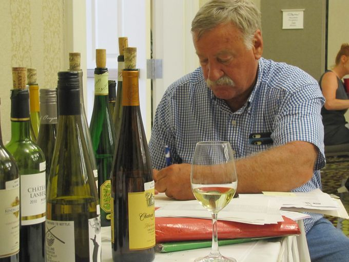 Jim Trezise of Penn Yan, president of the New York Wine & Grape Foundation, logs judges' scores Tuesday at the New York Wine & Food Classic at the Watkins Glen Harbor Hotel.  BOB JAMIESON / Elmira Star-Gazette