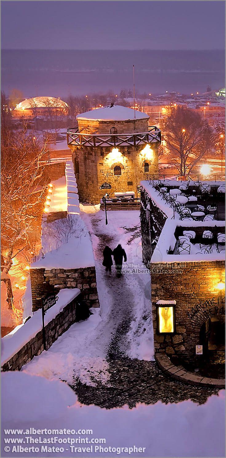 Two pedestrians among the medieval walls of Kalemegdan Citadel at dusk in heavy winter snowfall, Belgrade (Beograd), Serbia. Cityscape by Alberto Mateo, Travel Photographer.