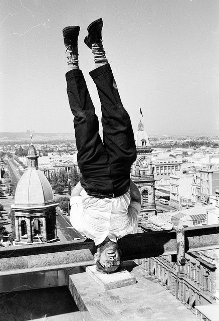 Listed under the category 'Immigration – Migrants at leisure', this Department of Immigration photograph from 1965 shows former Danish baker, Aage Pedersen, age 40, upside down on the roof of an Adelaide building. Pedersen had migrated from Flemlose, Denmark eight years earlier and planned to open a gymnasium.  This photograph comes from the collection of the National Archives of Australia. This image should be cited as NAA: A12111, 1/1965/23/9.