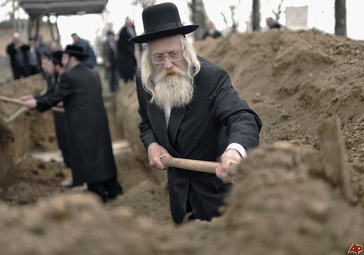 Rabi Meir Sclesinger of London, England, centre, takes part in the reburial of remains of Holocaust victims found in a mass grave in northern Romania, at the Jewish cemetery in Iasi, Romania, Monday, April 4, 2011. Members of Romania's Jewish community buried remains of about 60 Jews killed by Romanian troops during WWII and discovered in a mass grave in Popricani, northern Romania. (AP Photo/Radu Aneculaesi/Proimage)