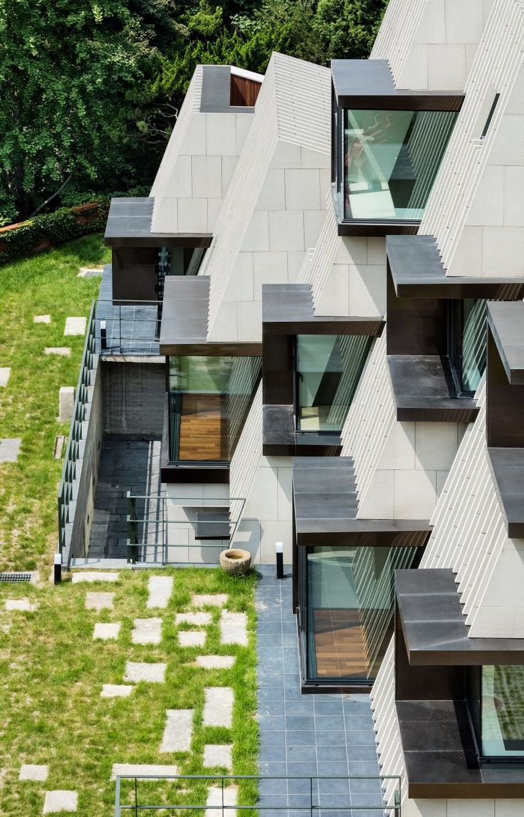 Limestone louvres and boxy windows cover the angled walls of this home outside Seoul
