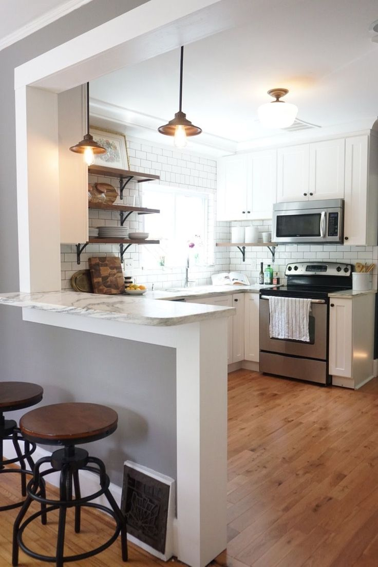 Vintage kitchen remodel. White shaker cabinets, marble countertops, white subway tile, and open shelving.
