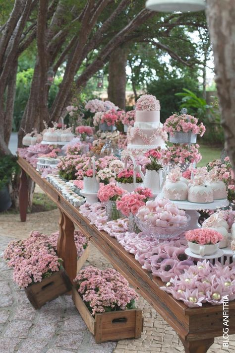 An overflow of pink on this rustic outdoor cake table!