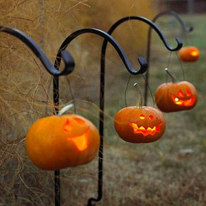 String wire through small Jack-o-Lanterns and hang them on iron shephard's hooks! ADORABLE!