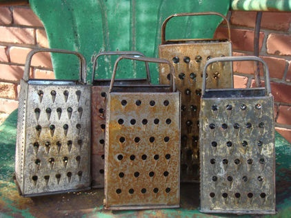 using old cheese graters as lanterns to light a walk way is actually a really cute idea.. especially since the really vintage and rustic ones look like little torture devices...