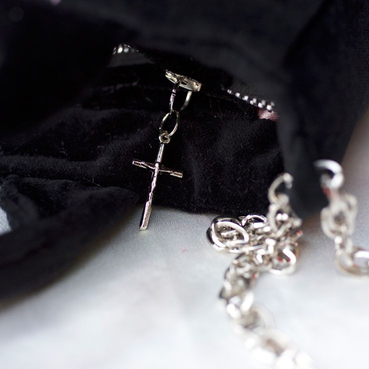 Zip fastening with a silver cross. Silver chain shoulder strap.  http://vitaocculta.com/handbags/handbags-littleBlackSaint-with-chain.htm