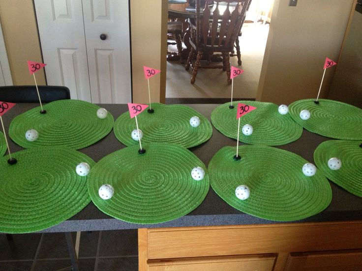 Golf themed birthday party. These center pieces were made from dollar store mats, plastic gold balls hot glued on, and wooden skewers for the flags. Add any age for the flags to make them personal!