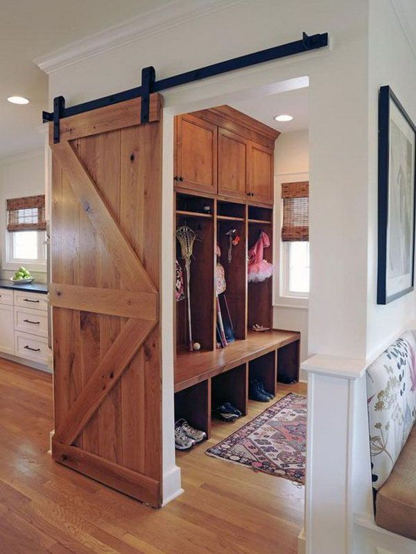 Wood mudroom. I love this area of house very much. It's really adorable with the warm wood color, mudroom view great barn door, wood flooring, boot storage, bench, hooks and expand upper shelf for hats.